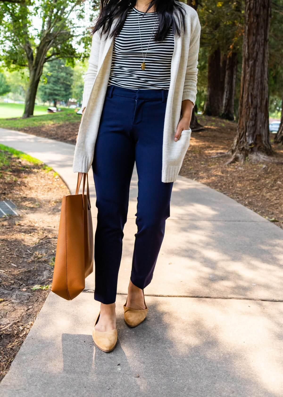 Comfy Casual Work Outfit: black and white striped long sleeve top + navy trousers + cream cardigan + gold pendant necklace + tan suede flats + tan tote