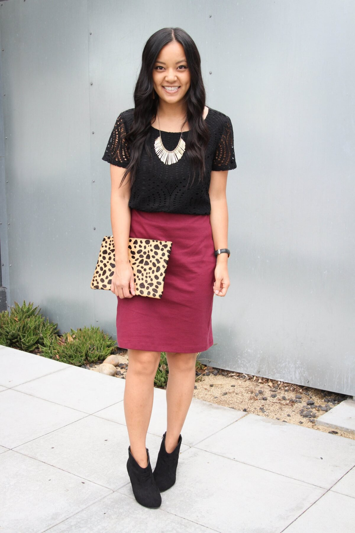 Dressy Outfit: solid-colored top black blouse + maroon skirt + black booties + gold statement necklace + gold earrings + leopard clutch