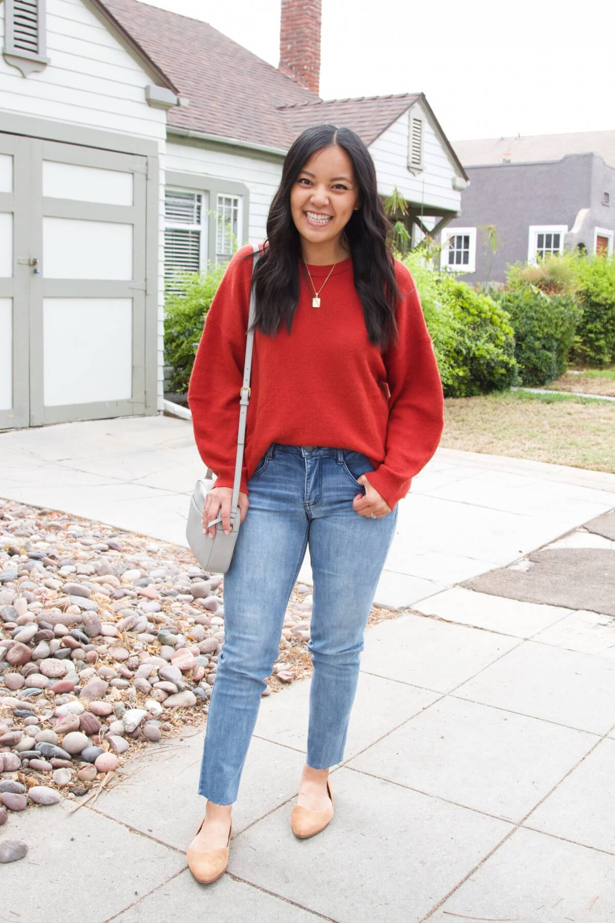Elevated Casual Outfit: solid-colored top rust balloon sleeve sweatshirt + light blue straight leg jeans + tan suede flats + gold short pendant necklace +gray crossbody bag