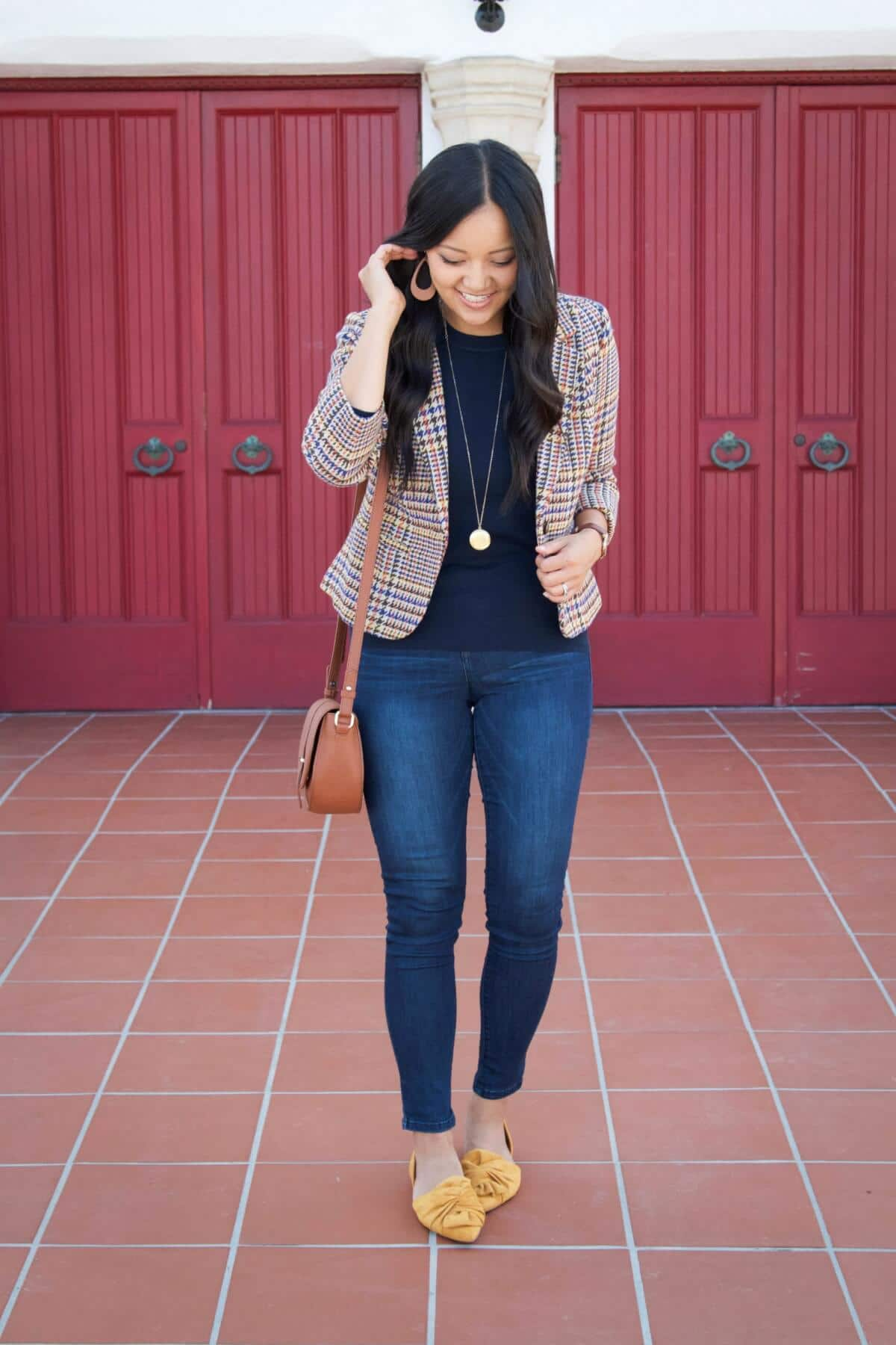 Elevated Casual Outfit: navy sweater solid-colored top + blue jeans + plaid blazer + tan earrings + gold pendant necklace + yellow flats + tan crossbody bag