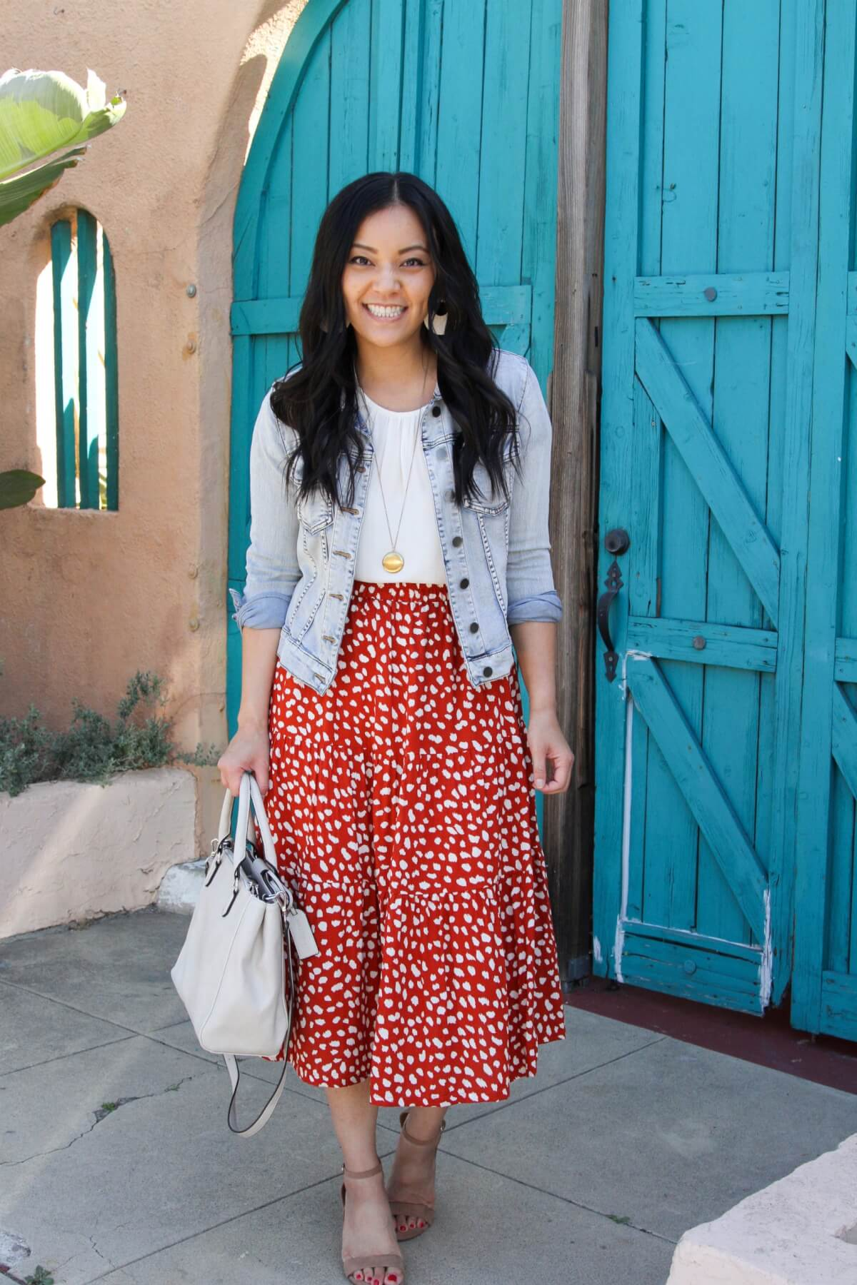 Dressy Casual Outfit: solid-colored top white blouse + red dot ruffle midi skirt + denim jacket + tan heeled sandals + gold pendant necklace + gray handbag