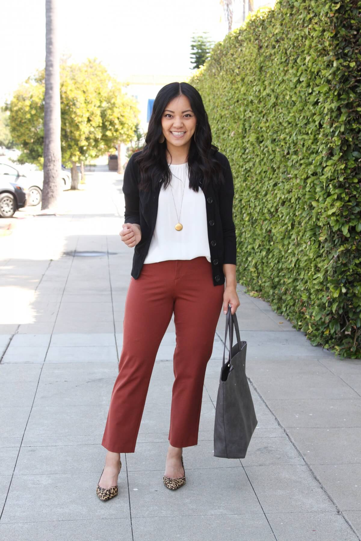 Business Casual Outfit: solid-colored top white blouse + black cardigan + rust straight let pants + gold pendant necklace + gray tote + leopard heels
