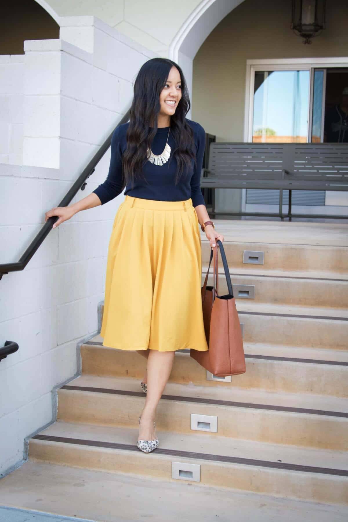 Dressy Outfit: solid-colored top navy sweater + yellow mid skirt + gold statement necklace + tan tote + leopard flats