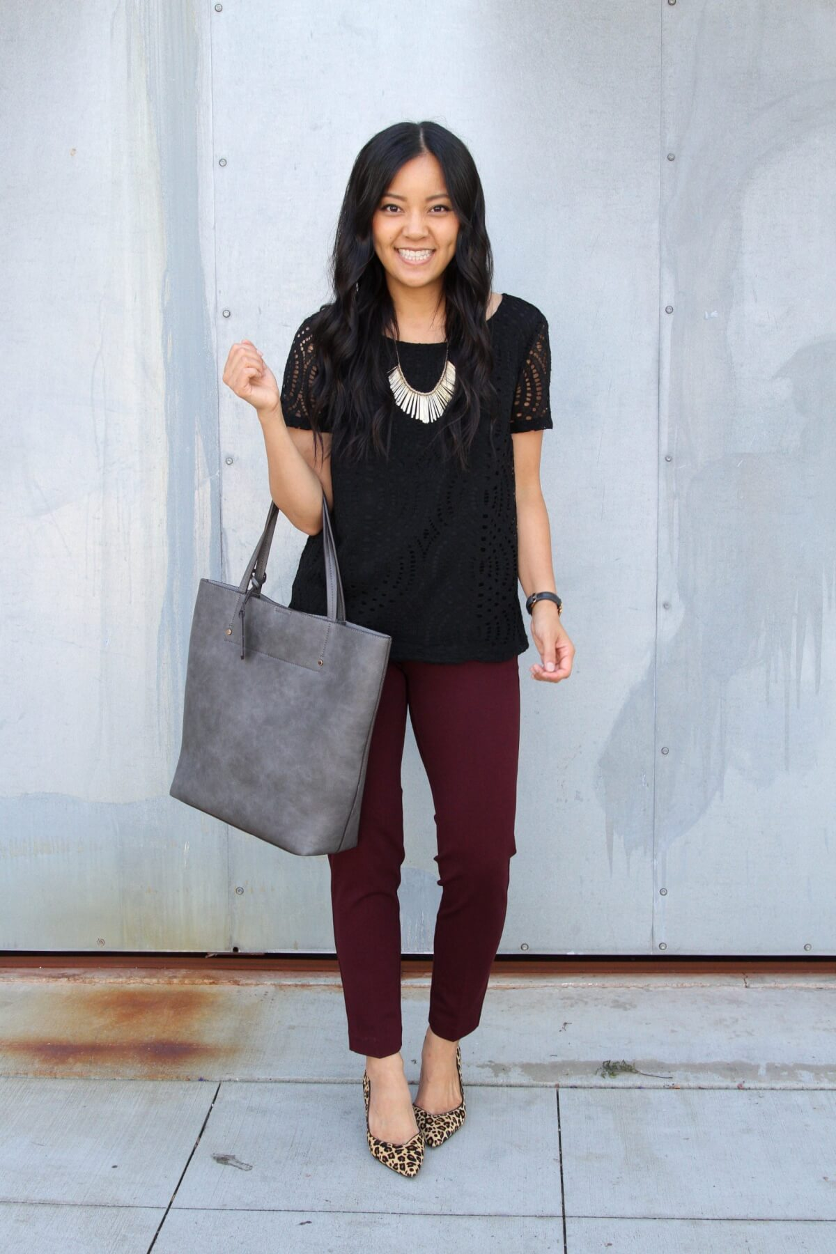 Business Casual Outfit: solid-colored top black blouse + maroon slacks + leopard heels + gold statement necklace + gold earrings + gray tote