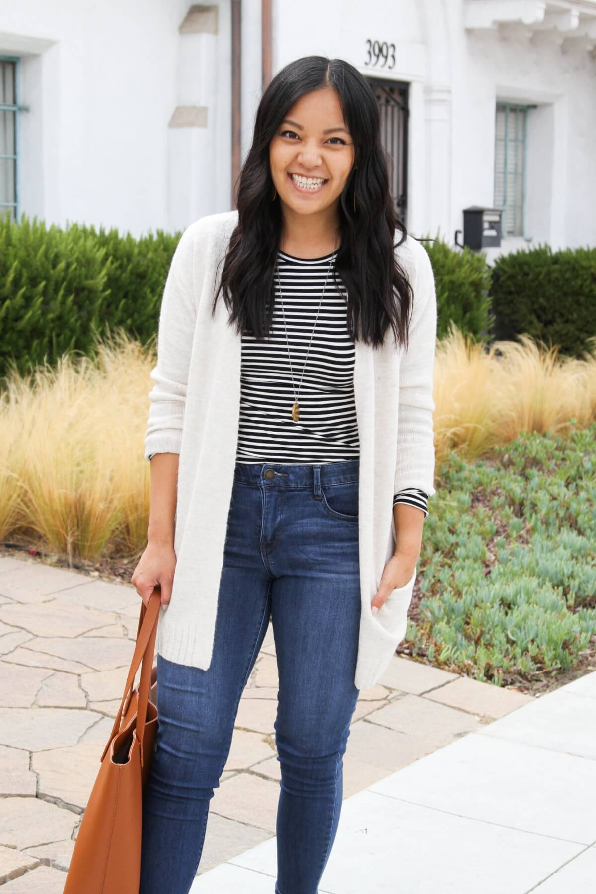 Elevated Casual Fall Outfit: black and white striped long sleeved tee + blue skinny ankle jeans + cream long cardigan + gold pendant necklace + tan tote