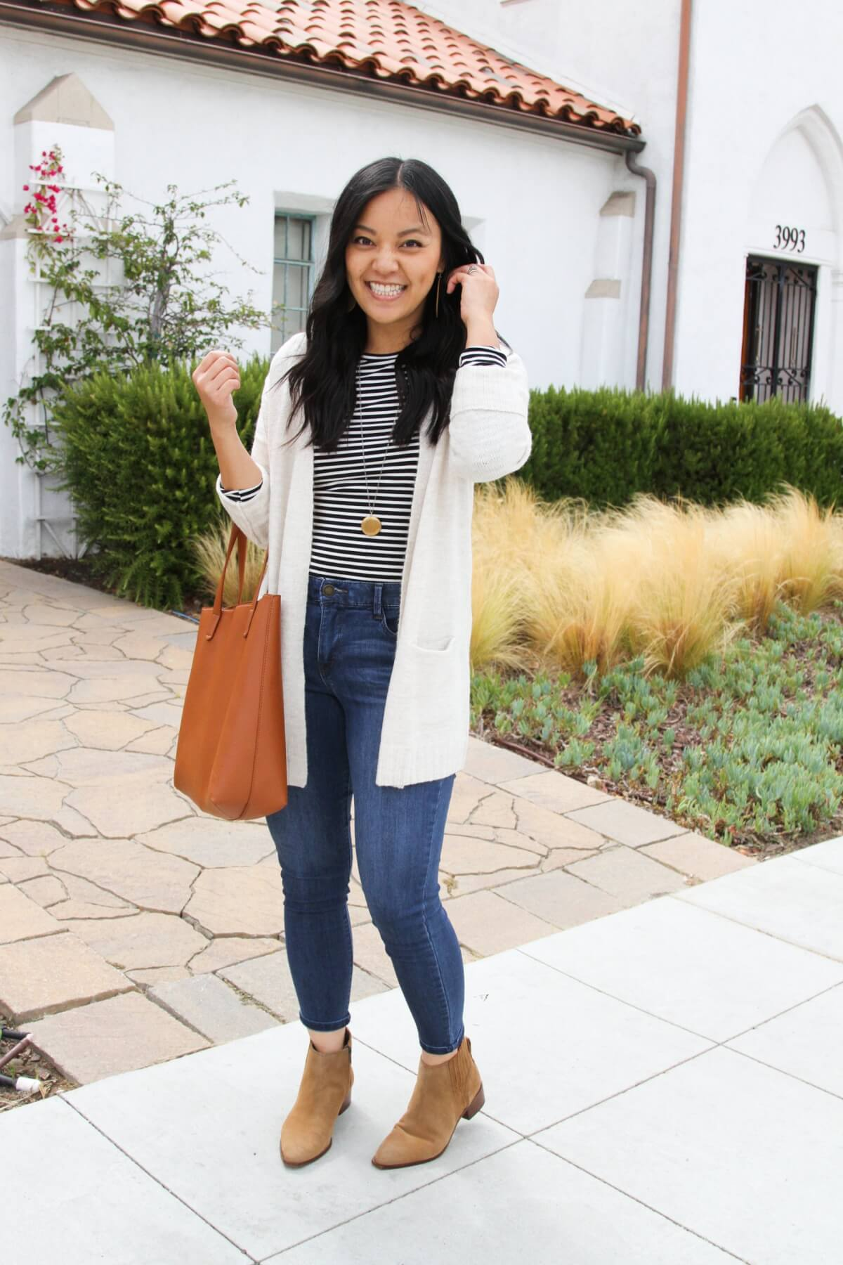 Elevated Casual Fall Outfit: black and white striped long sleeved tee + blue skinny ankle jeans + cream long cardigan + tan suede booties + tan earrings + gold pendant necklace + tan tote