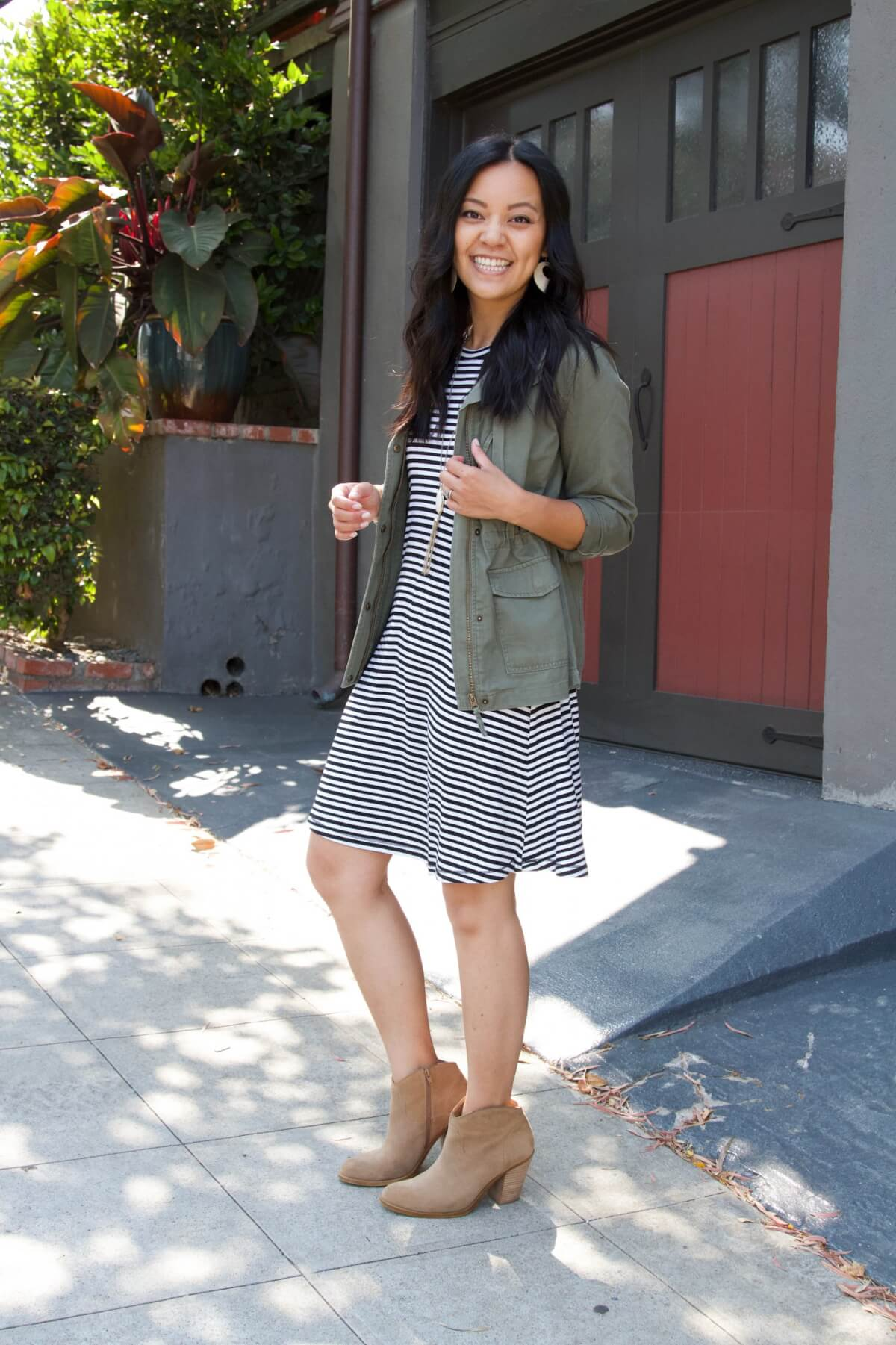 Summer to Fall Transition Nicer Casual Outfit: black and white striped dress + suede booties + olive utility jacket + white earrings + pendant tassel necklace