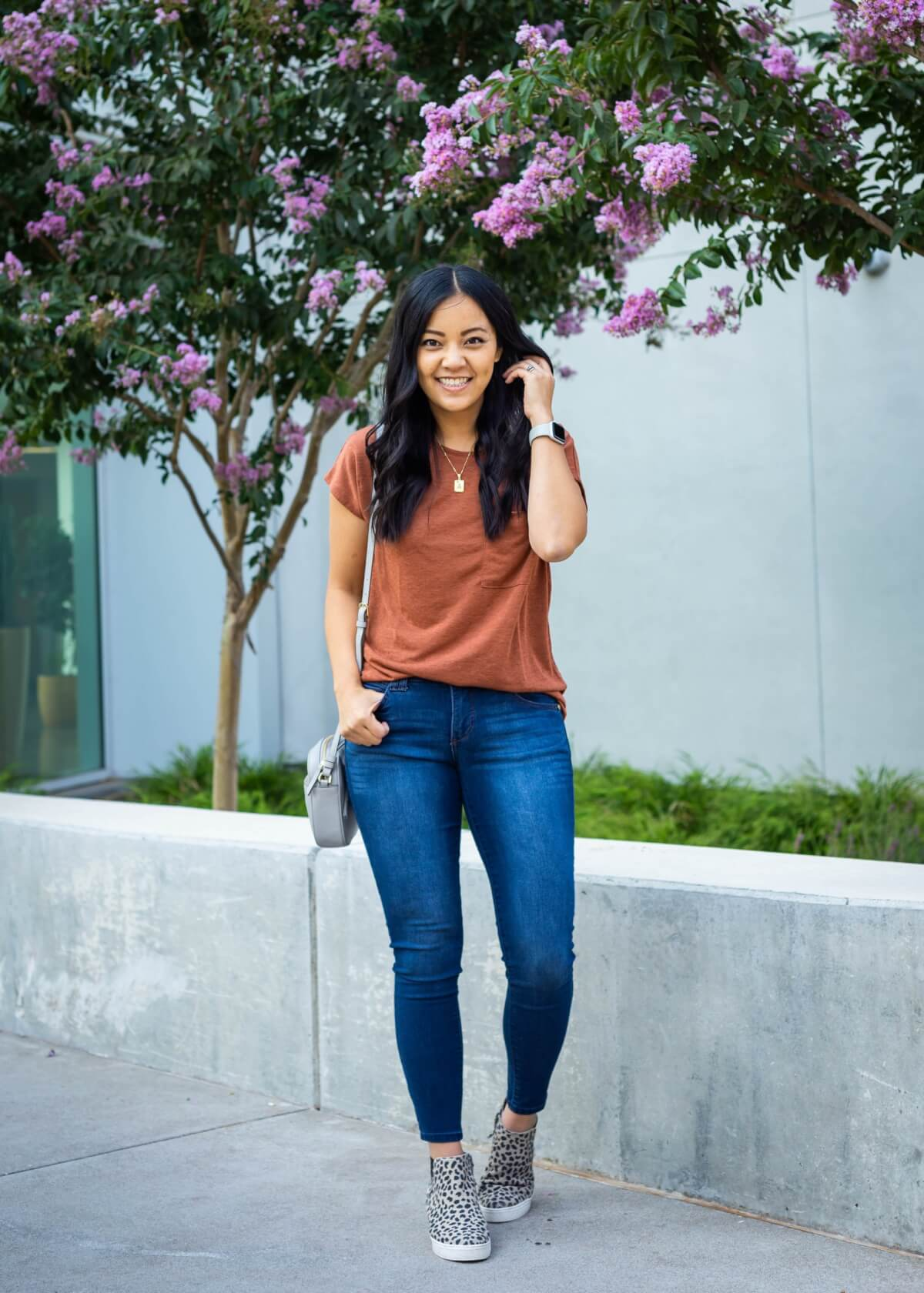 Casual Outfit: rust t-shirt + dark blue skinny jeans + leopard sneaker booties + gold pendant necklace + gray crossbody purse