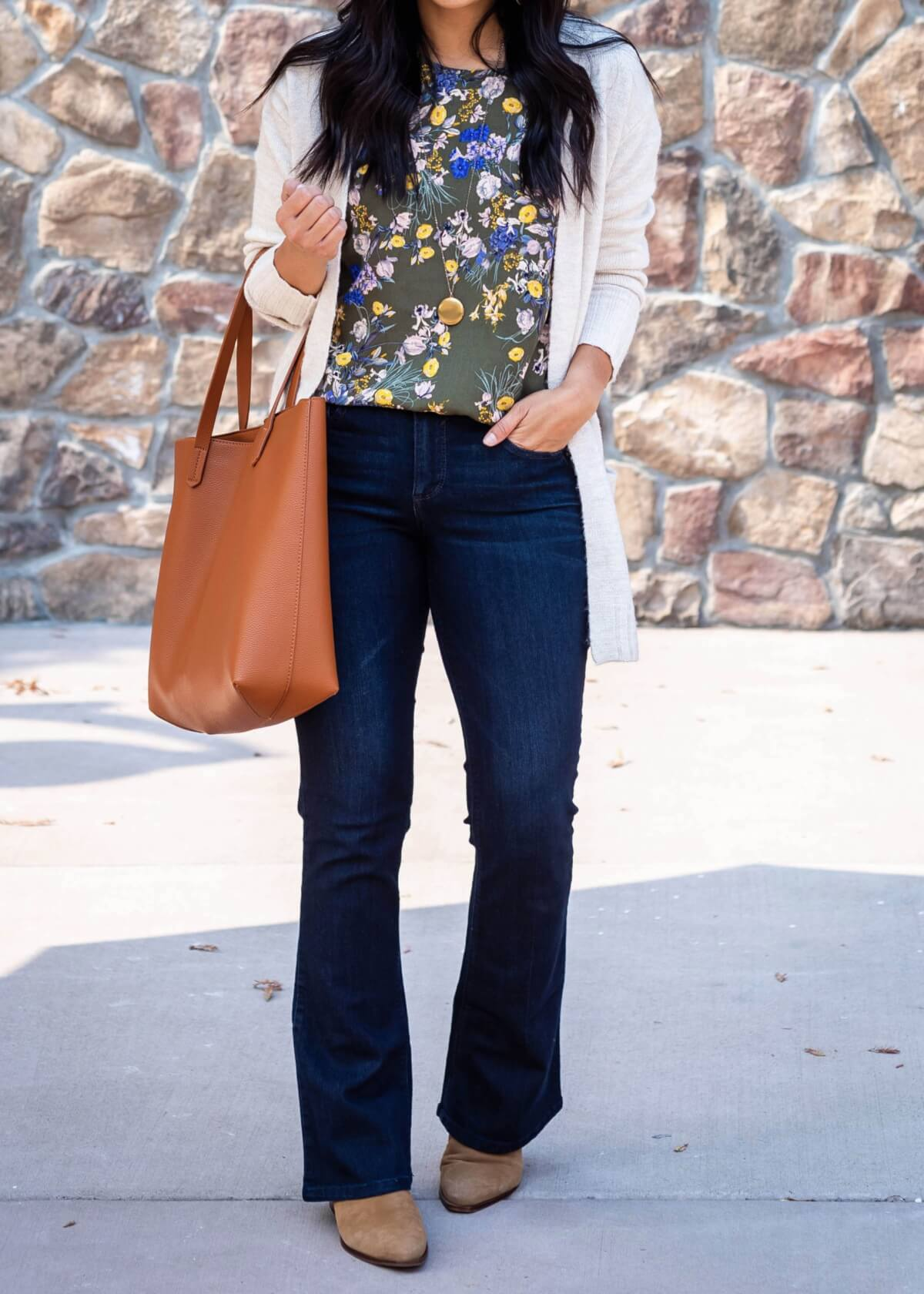 Dressy Casual Fall Outfit: olive floral print top + dark blue bootcut jeans + cream long cardigan + tan suede pointed toe booties + gold pendant necklace + tan tote close up