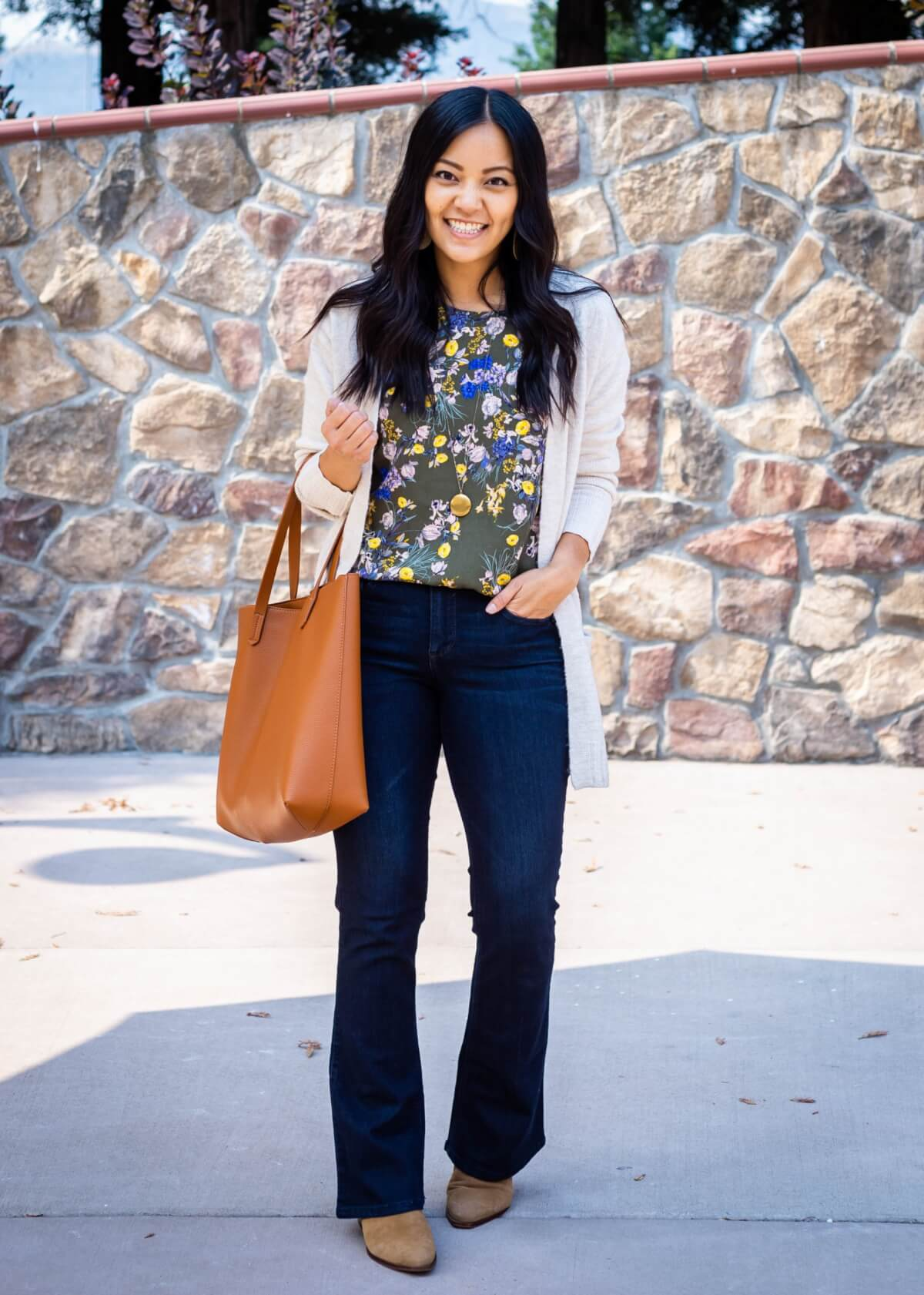 Dressy Casual Fall Outfit: olive floral print blouse + dark blue bootcut jeans + cream long cardigan + tan suede booties + gold pendant necklace + tan tote