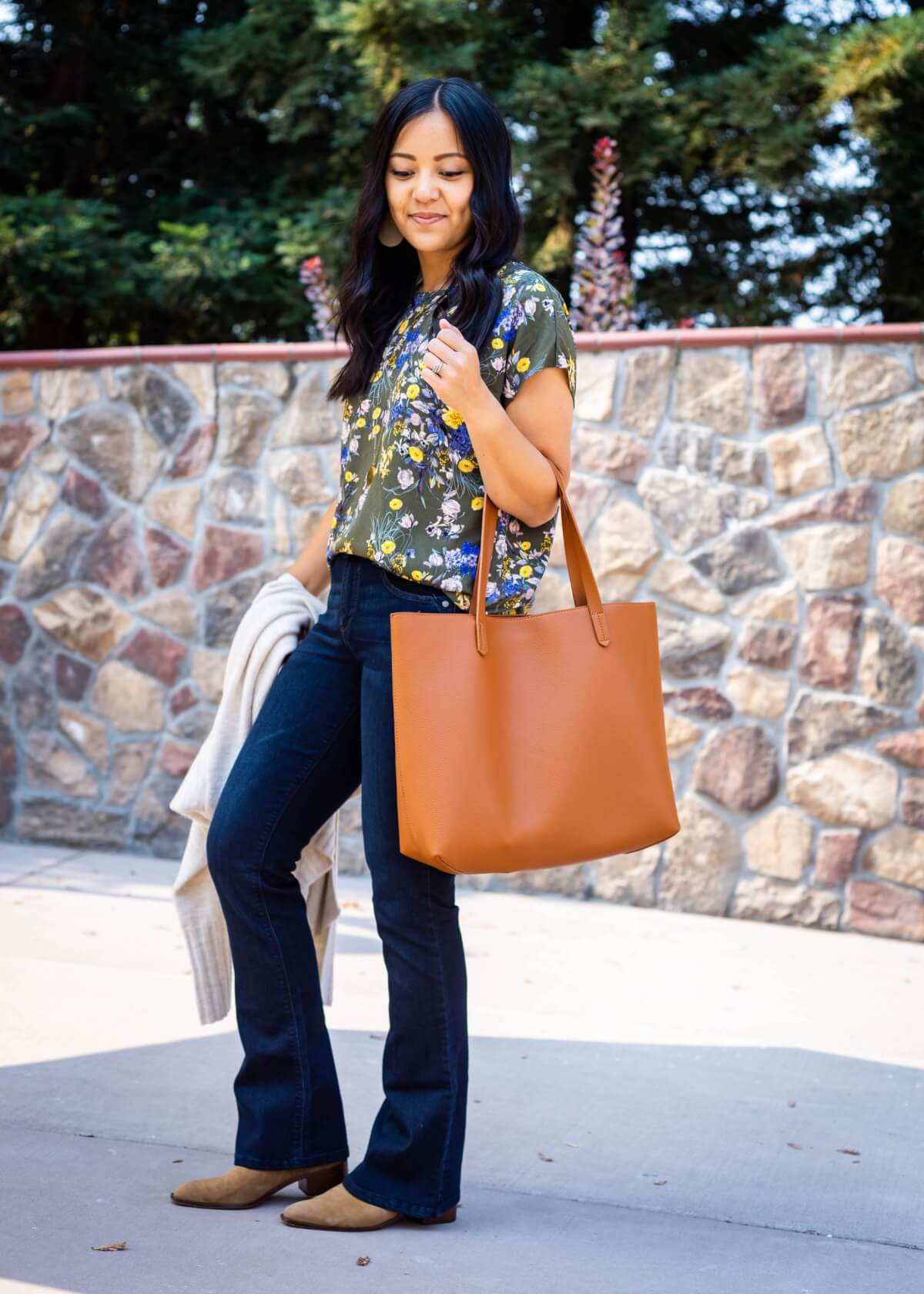 Dressy Casual Fall Outfit: olive floral print blouse + dark blue bootcut jeans + cream long cardigan + tan suede booties + yellow marigold earrings + gold pendant necklace + tan tote side