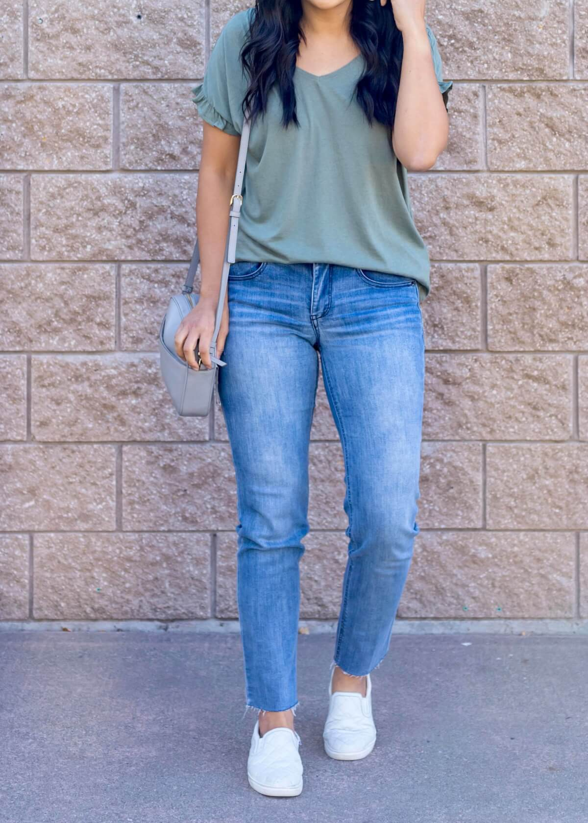 Casual Early Fall Outfit: sage green ruffle sleeve t-shirt + light blue straight leg raw hem jeans + white slip-on sneakers + gray crossbody bag close up