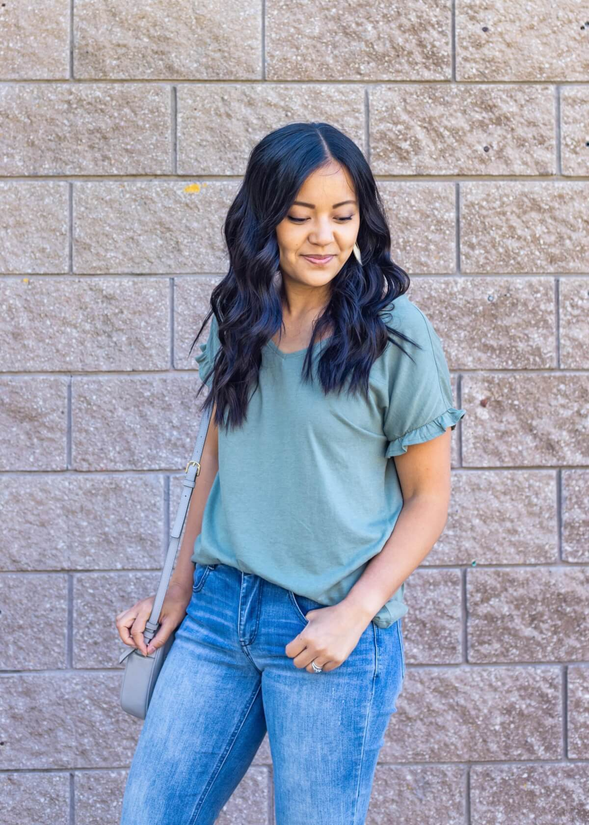 Casual Early Fall Outfit: sage green ruffle sleeve t-shirt + light blue straight leg raw hem jeans + white earrings + gray crossbody bag close up