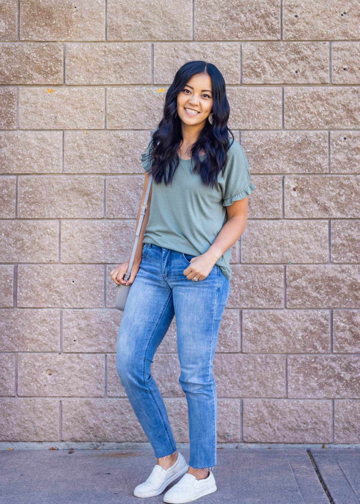 Casual Early Fall Outfit: sage green ruffle sleeve t-shirt + light blue straight leg raw hem jeans + white slip-on sneakers + white earrings + gray crossbody bag