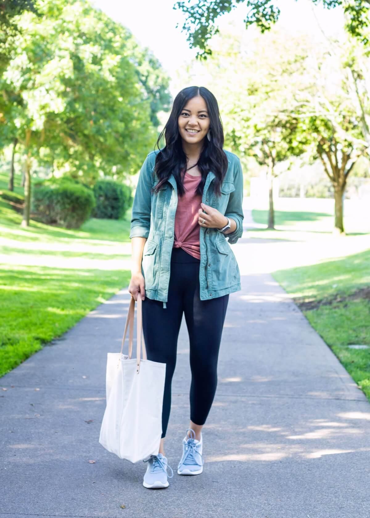 Casual Fall Outfit: knotted dusty pink tee + black leggings + green utility jacket + gray lace up sneakers + white canvas tote