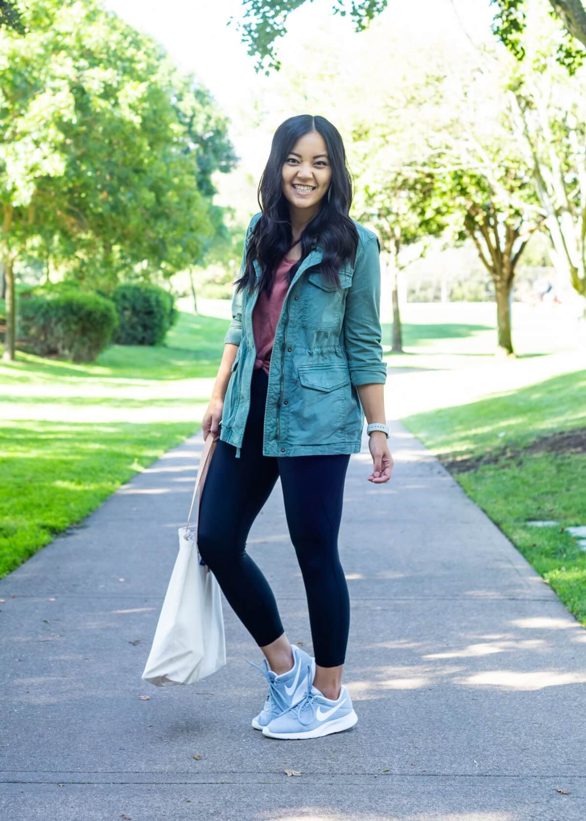 Casual Fall Outfit: dusty pink tee + black leggings + green utility jacket + gray sneakers + white canvas tote side