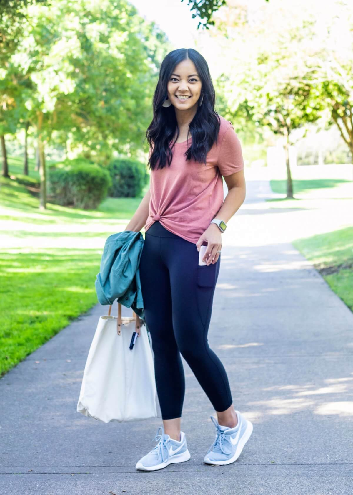 Casual Fall Outfit: dusty pink tee + black pocket leggings + green utility jacket + gray sneakers + white canvas tote side