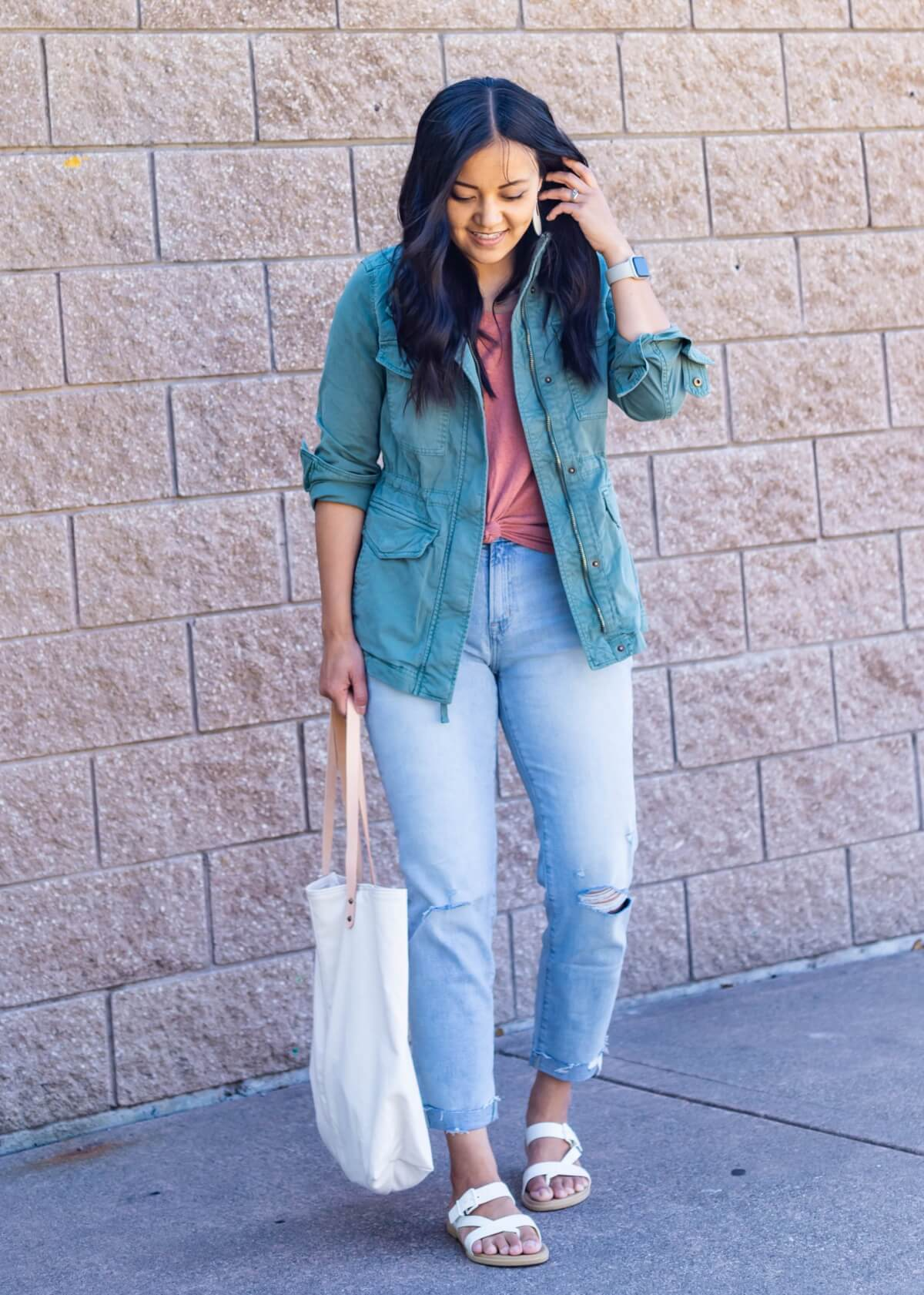 Casual Fall Outfit: pink tee + light wash distressed straight leg jeans + green utility jacket + white earrings + white footbed sandals + white canvas tote