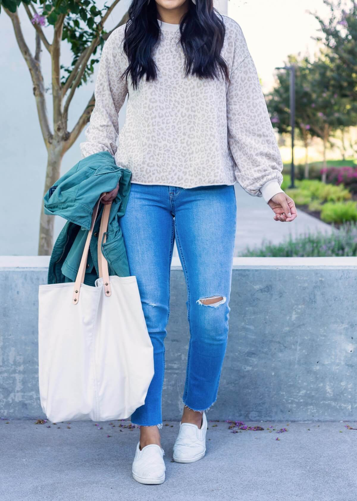 Casual Fall Outfit: light pink beige leopard sweatshirt + light wash distressed raw hem straight leg jeans + Gap green utility jacket + white slip-on shoes + white canvas tote bag