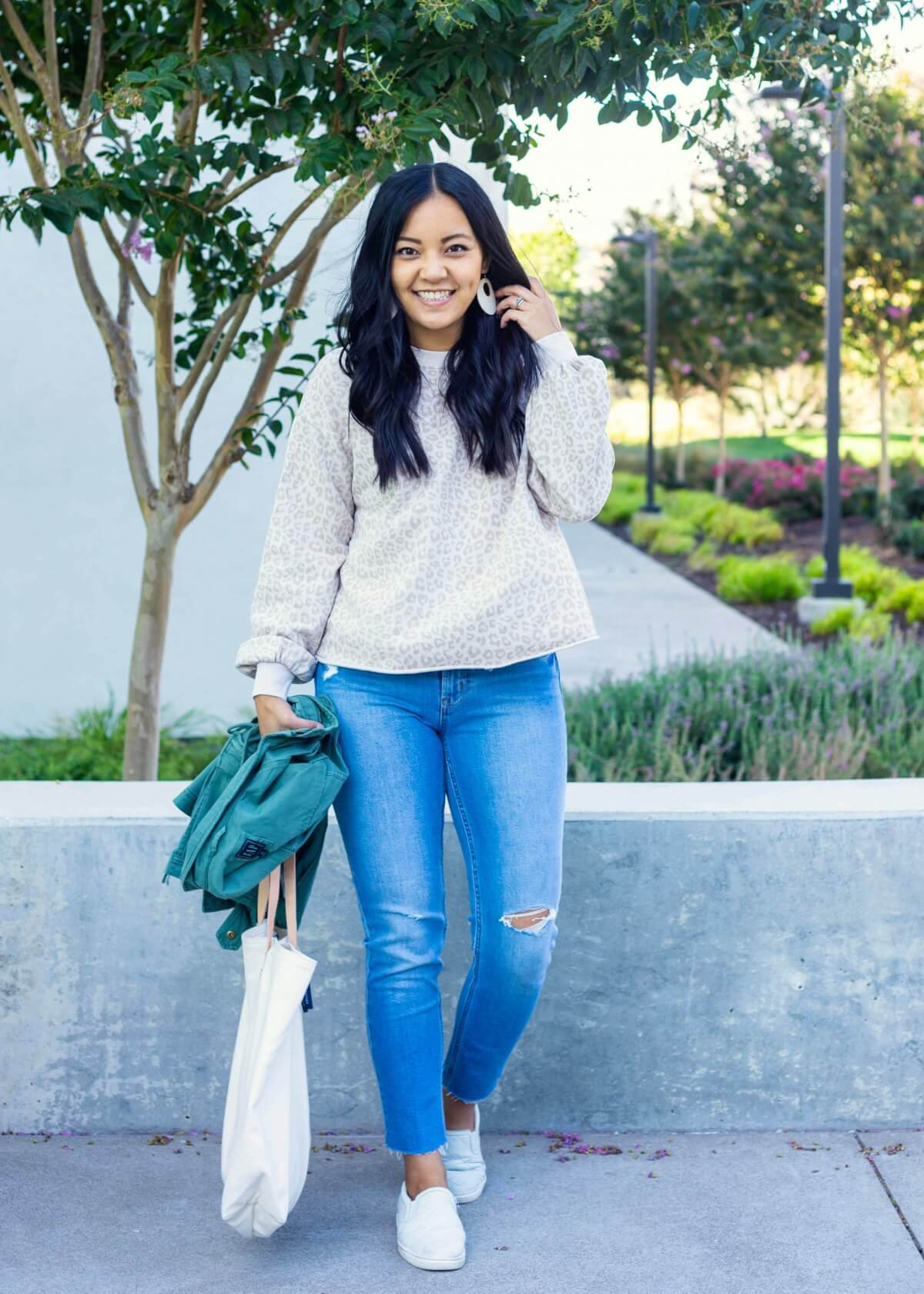 Casual Fall Outfit: light pink beige leopard puff sleeve cropped sweatshirt + light wash distressed straight leg jeans + green utility jacket + white slip-on sneakers + white earrings + white canvas tote