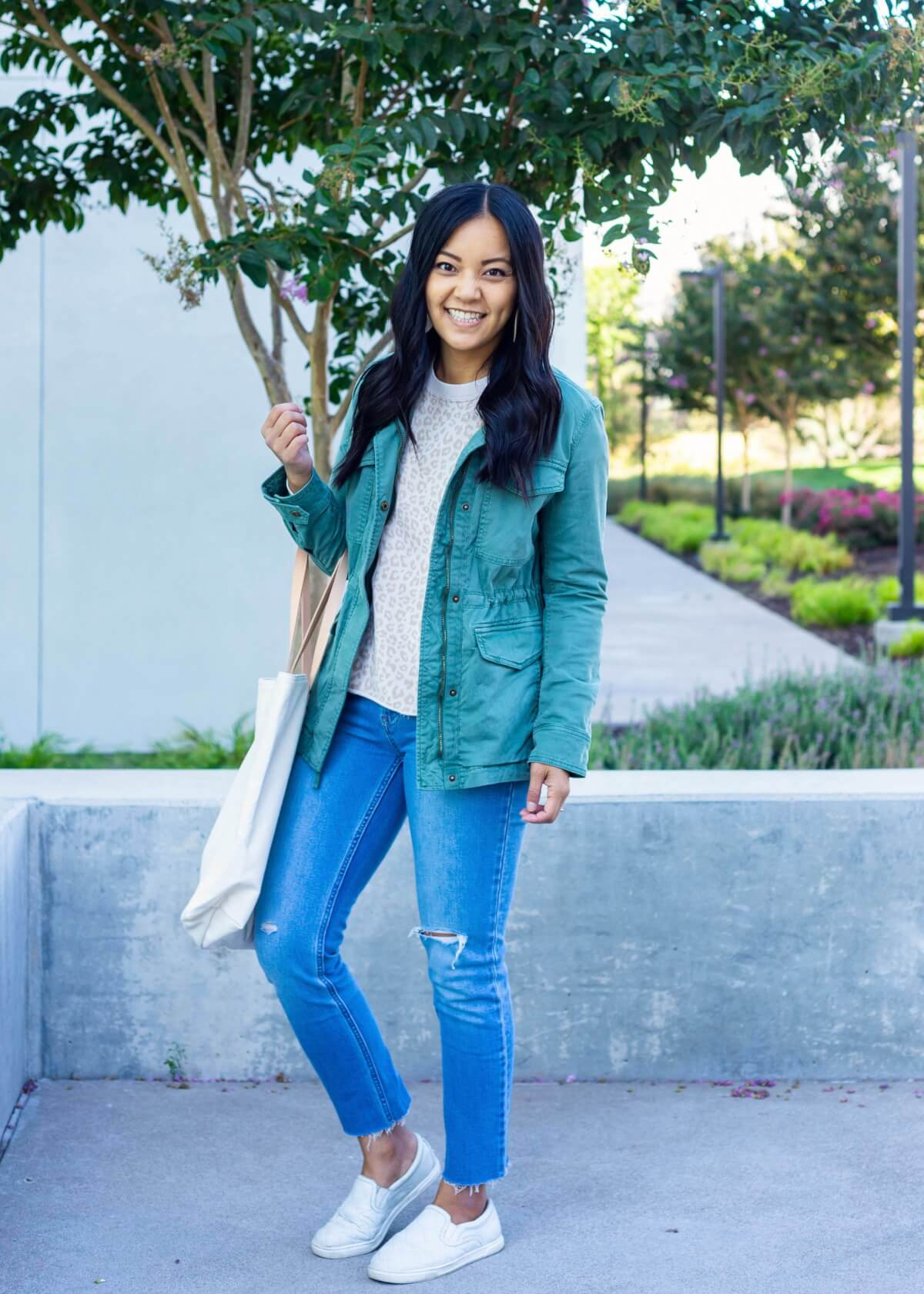 Casual Fall Outfit: light pink beige leopard sweatshirt + light wash distressed raw hem straight leg jeans + Gap green utility jacket + white slip-on shoes + white Nickel & Suede earrings + white canvas tote bag side