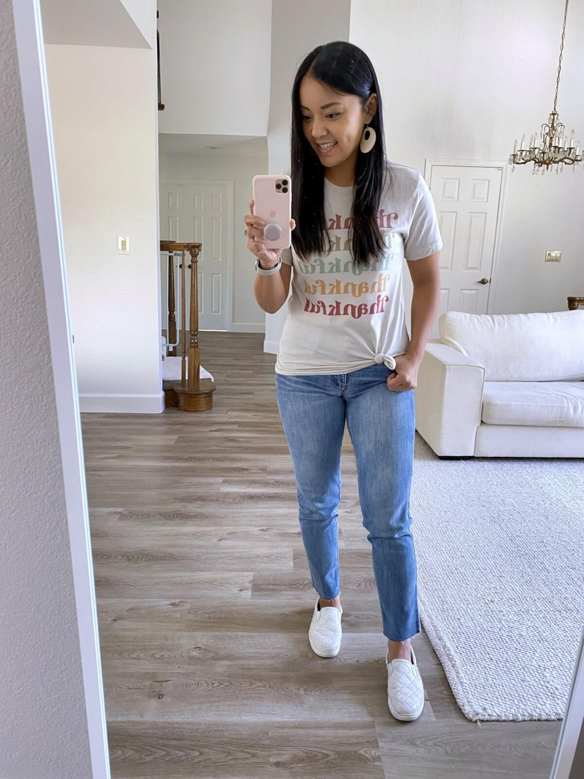 Casual Outfit Early Fall: thankful t-shirt + light straight leg jeans + white earrings + white slip-on sneakers
